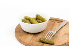 Small pickles in the white bowl and pickle on the fork.  Royalty Free Stock Images