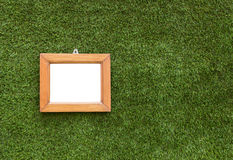 Small picture frame hangings on artificial grass Royalty Free Stock Photography