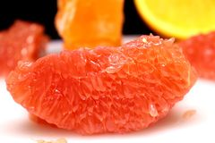 A small piece of grapefruit close up, an isolated and juicy piece of fruit pulp that you want to eat right away stock image