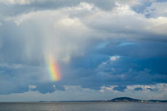 Small piece of Rainbow Over Sea Against cloudy  Sky Royalty Free Stock Photos