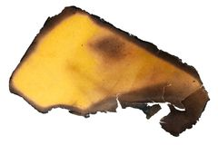 A small piece of yellow aged vintage paper with burned black e stock images