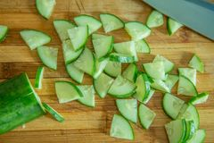 Small pieces of cucumber for salad on a wooden cutting board and cook knife Royalty Free Stock Photo