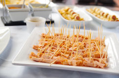 Small pieces of ham canapes lined up on white plate Royalty Free Stock Photos