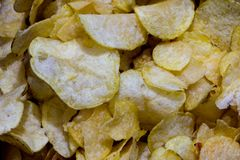 Small pieces of the potato chips. Macro shoot of small pieces of the salty and fried potato chips Stock Image
