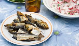 The small pieces of smoked fish on a platter. Table setting Stock Photography