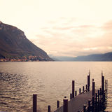 Small pier and calm water. Cloudy day on Como lake Royalty Free Stock Photography