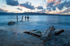 Small pier. Sunset over the Strait of Messina, the long exposure for low light creates silky sea while Stock Image