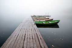 Small Pier With Boats On Lake In Foggy Morning Stock Image