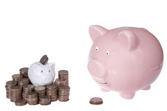 Small piggy bank with piles of quarters, large piggy bank with s Royalty Free Stock Photography