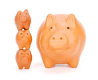 Small piggy banks superimposed near big one Royalty Free Stock Images