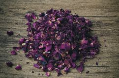Dried rose petals on textured background. A small pile of dried pink flower rose petals on a brown wooden textured surface or background stock photo