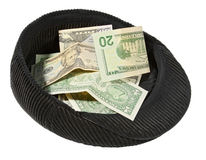 Small pile of money lies in a cap. Stock Images