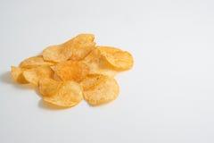Small pile of potato crisps on white. Background. low angle shot Stock Photo