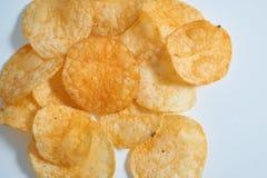 Small pile of potato crisps on white. Small pile of spicy potato cheese crisps on white background. top angle closeup shot Royalty Free Stock Photos