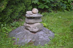 Small pile of stones  in a garden. Small pile of stones in a garden. Zen attitude, rocks and grass, grey and green Royalty Free Stock Image