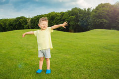 Small pilot airplane dreamer. Little baby boy standing on the green grass. Summer walk. Hands to the side. Greeting and singing. Joy hand gestures. Empty t-short Royalty Free Stock Photo