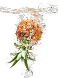 Small pineapple falling in water on white Stock Photos