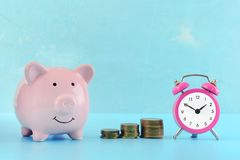 A small pink alarm clock, three stacks of coins and a piggy bank on a light blue background. The symbol of the. Accumulation of money. Beautiful bright photo Stock Images