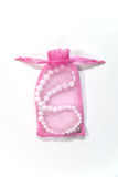 Small pink bag with pearl. On a white background Stock Photos