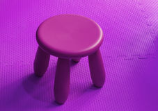 Small pink plastic stool for kids isolated on soft floor indoor Royalty Free Stock Image