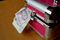Small pink strongbox with silver edges holding thick pack of money (Czech Crowns, CZK). As a symbol of protected and safely stored wealth Royalty Free Stock Photos