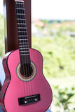 Small pink ukulele guitar on a tropical background. Music instrument. Stock Photo