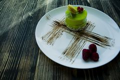 A small pistachio cake with a green coating and decorated with viburnum, confectionery dressing on a black background. Side view royalty free stock photo