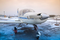 Small plane is at the airport in non-flying weather, winter Royalty Free Stock Photos