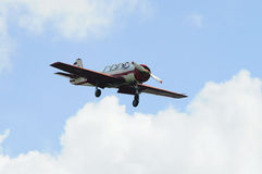The small plane flies against clouds. Royalty Free Stock Image