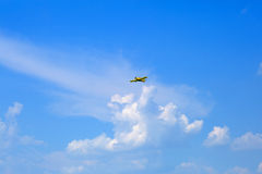 The small plane is flying against the blue sky. Royalty Free Stock Photos