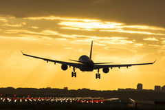 Small plane landing during sunrise. Stock Image