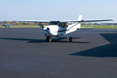 Small Plane Ready to Taxi. A small passenger airplane gears up to taxi, its propeller blurred in motion. Tail number and other identifying marks have been healed Stock Image