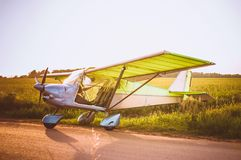Small plane in the sky and on the field. Vintage photo. Even Stock Photos