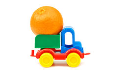 Small plastic colorful toy truck with one mandarin fruit Stock Photo