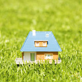 Small plastic house on green grass Stock Image