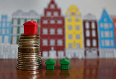 Small plastic house model on top of stacked coins. Moscow, RUSSIA. Small plastic house model on top of stacked coins on colorful background with houses royalty free stock images