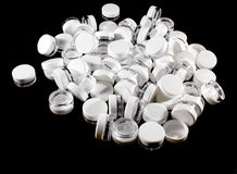 Small Plastic Jars with Lids On Black. Plastics cosmetics Jars and screwed on lids on a black background Stock Photos