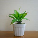 Small plastic plant in ceramic pot on table Royalty Free Stock Photos