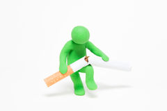 Small plasticine puppet breaks a cigarette Royalty Free Stock Photos