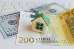Small plasticine white toy house with green roof stands on the banknotes of dollar and euro lying on laptop. Royalty Free Stock Photography