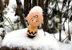 Small plastick smiling toy covered with snow. Closeup photo. Winter funny background. Childhood concept royalty free stock images