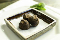 Small plate of chocolate truffles. Small plate of three chocolate truffles on white plates Royalty Free Stock Image