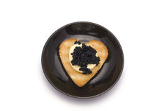 Small Plate with Heart-shaped Toast with Caviar. Isolated on white Royalty Free Stock Photo