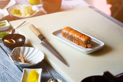 Small plate with sushi rolls. Knife lying beside sushi. Meal cooked at japanese restaurant. Dish prepared at sushi cafe Stock Photos