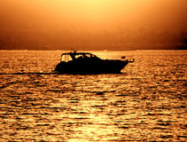 Small Pleasure Boat Craft Sailing at Sea at Sunset. Pleasure boat sailing on calm waters near shore at sunset with sea coastline shoreline glowing in amber color Stock Image