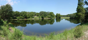Small pond. A panoramic shot of a small pond, lush vegetation surrounding it Stock Images