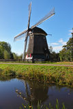 The small pond and  ancient windmil. Stock Photography