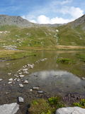 Small pond at the Col Agnel. Alpine landscape with stone outcropping on the surface of a pond at high altitude. Col Agnel, Border Italy-France Stock Photo