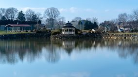 A small pond with a gazebo reflecting in the water, on a beautiful, calm and quiet day, Lancaster County, PA royalty free stock photography