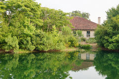 Small pond and house Royalty Free Stock Image